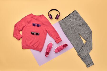 Hipster DJ trendy colorful autumn Outfit. Fall fashion Flat lay. Pink jumper, Stylish sneakers, headphones. Creative Woman Clothes Accessories layout. Fall Girl fashionable autumnal color.