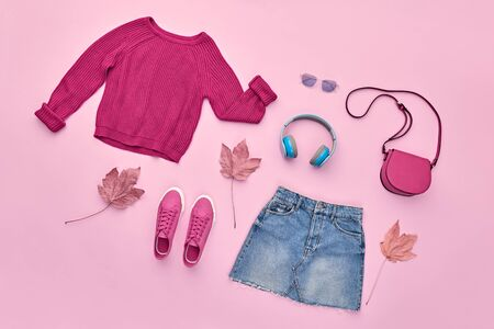 Fall fashion Flat lay. Trendy jumper, Stylish hipster sneakers, headphones, denim, autumn Maple Leaf. Creative Woman Clothes Accessories layout. Fall Girl fashionable Outfit, autumnal pastel color
