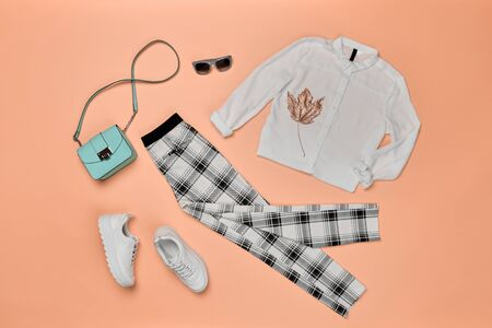 Fall fashion Flat lay. Trendy shirt, Stylish trousers, hipster sneakers, autumn Maple Leaf. Creative Woman Clothes Accessories Set. Fall Girl fashionable Outfit, autumnal orange color.