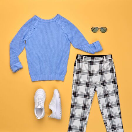 Fall fashion Flat lay. Trendy autumn blue jumper, Stylish trousers, hipster sneakers. Creative Woman Clothes Accessories layout. Fall Girl fashionable Outfit, autumnal orange color. Imagens