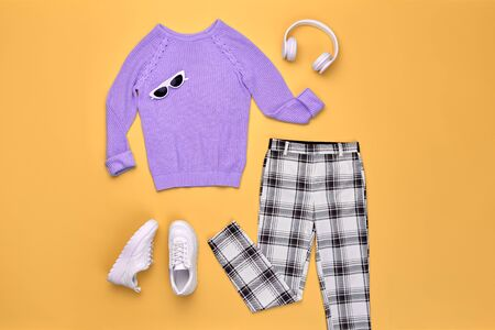 Hipster DJ trendy colorful autumn Outfit. Fall fashion Flat lay. Purple jumper, Stylish sneakers, headphones. Creative Woman Clothes Accessories layout. Fall Girl fashionable autumnal color.