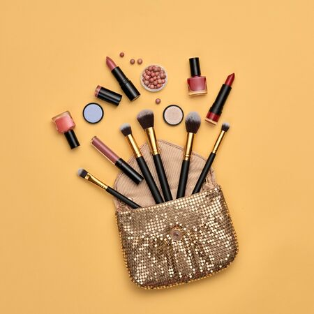 Woman beauty cosmetic makeup accessories Flat lay. Fashion Minimal autumn Set. Trendy Design glamor Clutch, brushes. Art Concept fall Style. Creative fashionable autumnal orange color.