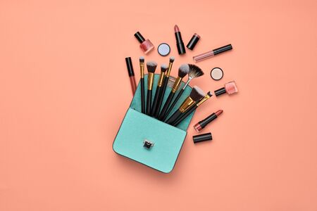 Fashion cosmetic makeup autumn Set. Collection beauty product on coral art background. Trendy accessories Brushes Eyeshadow, handbag. Creative Flat lay, make up fall cosmetic fashionable concept