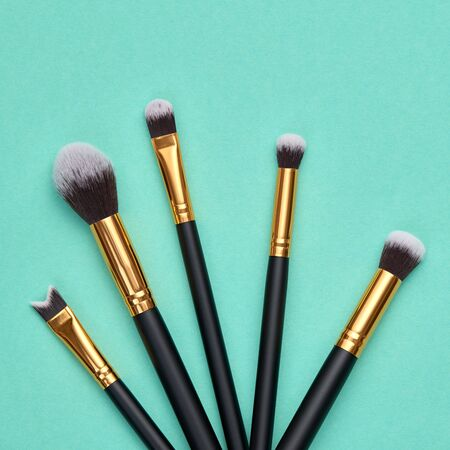 Fashion cosmetic makeup autumn Set. Minimal. Collection beauty accessories on green background. Trendy Brushes, art fashionable layout. Creative Design Flat lay, make up fall autumnal concept
