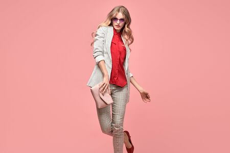Fashionable blonde woman in Trendy autumn spring outfit, stylish hairstyle, makeup. Joyful lady in jacket dance on pink. Cheerful girl, stylish fashion accessories, beauty style Stockfoto