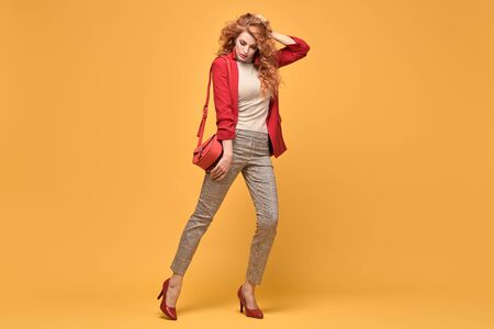 Fashionable woman in Trendy autumn spring outfit, stylish wavy hair, makeup. Joyful lady in red jacket smiling dance on orange. Cheerful girl, stylish fashion accessories, beauty style Stockfoto