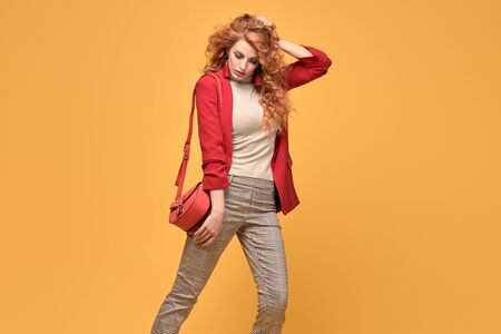 Fashion. Beautiful woman in autumn red jacket, trendy curly hair, make up. Adorable well dressed redhead girl on orange. Gorgeous fashionable lady in red, hairstyle, makeup. Creative beauty shot