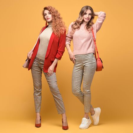 Two fashionable woman sisters in Trendy autumn red pink outfit, stylish hair, makeup. Joyful friends in jacket, jumper smiling on orange. Cheerful girl, stylish fashion accessories, beauty style