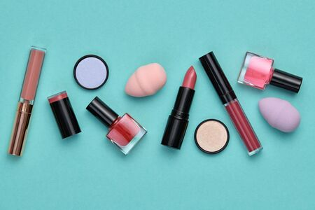 Fashion pink beauty product layout. Woman Essentials cosmetic makeup coral Set. Collection beauty accessories, lipstick. Minimal. Colorful art Design Flat lay. Creative make up cosmetic on mint green Stock Photo