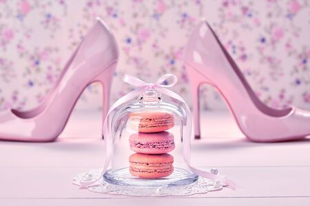 Romantic creative Love concept. Fashionable wedding accessories set. Bride essentials. Macarons, pearl, luxury beige bridal glamor fashion shoes heels. Floral vanilla background. Vintage Stock Photo