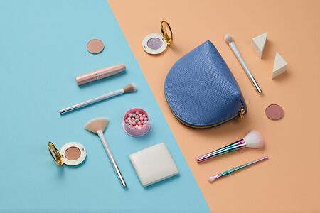 Cosmetic makeup accessories layout. Fashion creative minimal Set. Trendy Design Clutch, lipstick brushes. Art Concept colorful pastel Style. Beauty cosmetic make up tools, fashionable flat lay on blue Stock Photo