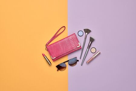 Woman beauty cosmetic makeup accessories Flat lay. Fashion Minimal Set. Trendy Design Clutch, lipstick brushes. Art Concept colorful Style. Creative fashionable cosmetic, orange purple color.