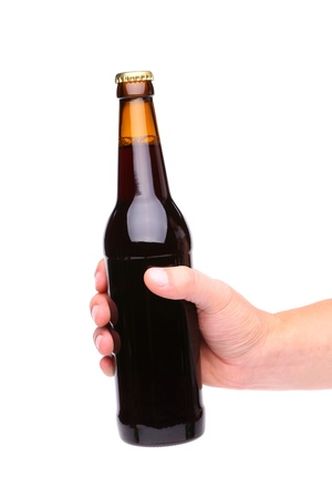 holding close: A hand holding up a brown beer bottle without label over a white background vertical format
