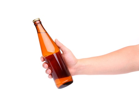 holding close: A hand holding up a yellow beer bottle without label over a white background vertical format Stock Photo