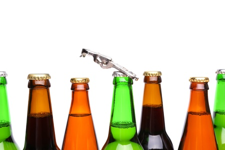 closing time: Top bottles of beer and a opener on the white backgrouind. Stock Photo