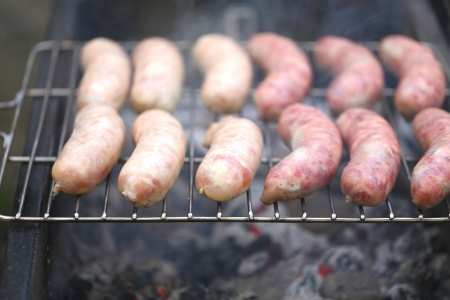 Fresh sausage grilling outdoors on a  barbecue grill. photo