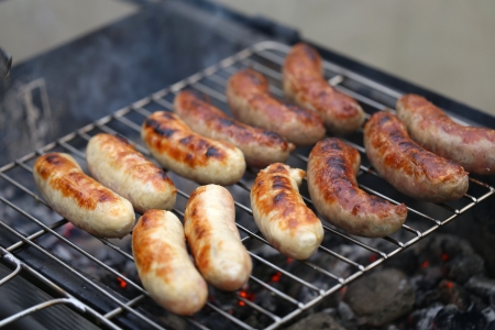 Sausages on grill on a whole background photo