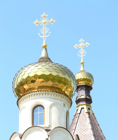 Golden dome of the Orthodox church on the blue sky background partially covered with snow. photo