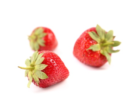 Green tails of strawberries are located in foreground photo