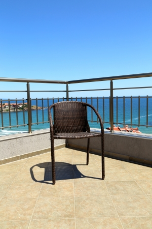 stanza: Lonely armchair against the sea rolling in the sky Stock Photo