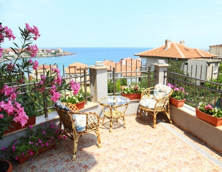 Beautiful patio surrounded by flowers with a sea view photo