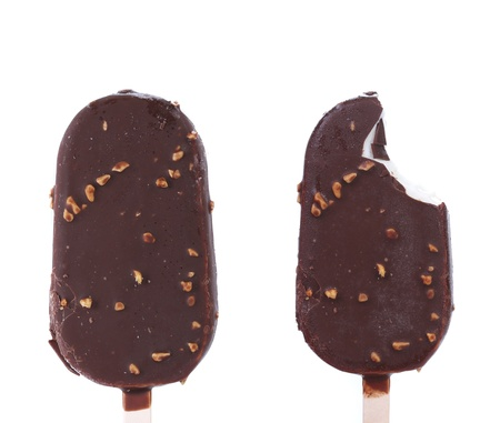 chock: Chocolate-coated blocks of ice cream on stick. White background. Stock Photo