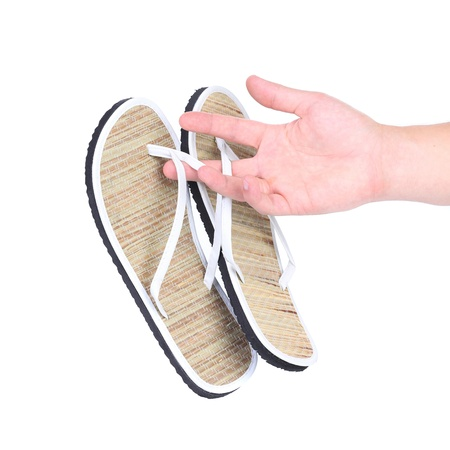 Pair of striped flip-flop sandals in hand. White background. photo