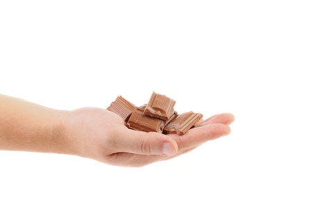 morsel: Hand holds tasty morsel of milk chocolate. White background.