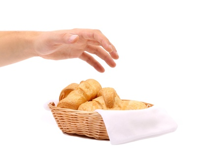 reaches: Hand reaches for the croissants in a basket. White background.