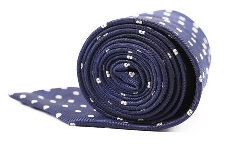Folded blue tie with white speck. White background. photo
