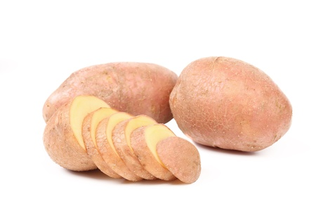 Ripe red potatoes and slices on a white background photo