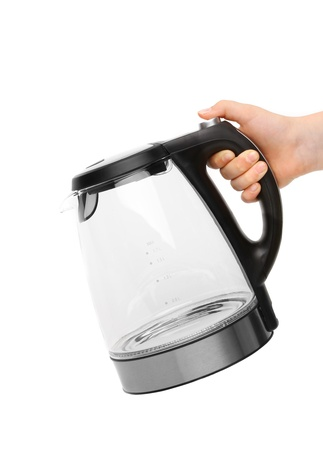 electric tea kettle: Hand holds glass electric kettle. White background.