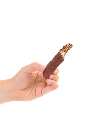 honeycombed: Hand holds bitten chocolate bar. White background.