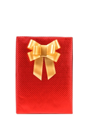 Red present box with spots and golden bow. White background. photo