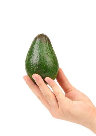 Hand holds avocado. Isolated on a white background. photo