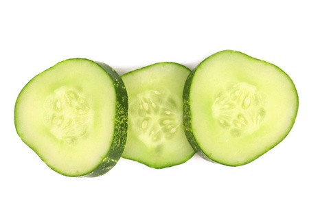 Slices of fresh cucumber. Isolated on a white background. photo