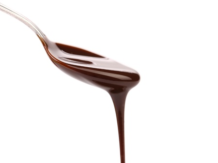 chocolate syrup leaking from spoon on white background with clipping path photo