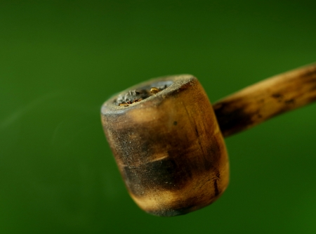 pernicious: Simple tobacco pipe. Isolated on a green background.