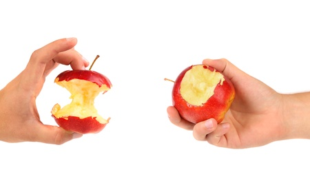 pome: Hands holds core and nibbled apples. White background.