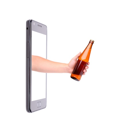 Hand with bottle of beer climbs from phone  photo
