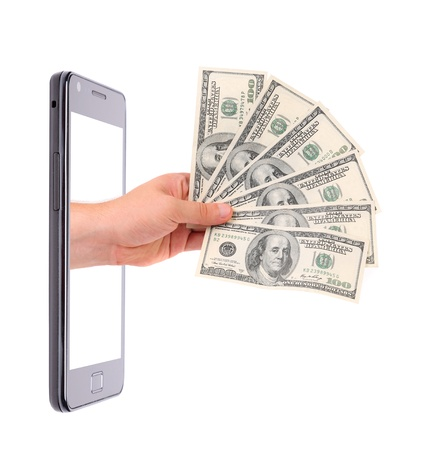 Hand with fan of hundred-dollar bills protrudes from phone. White background. photo