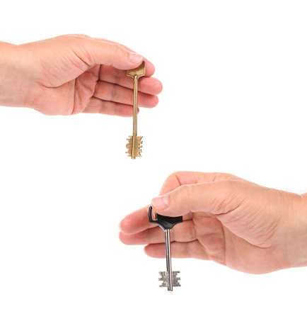 Hands holds modern steel-plastic and bronze key. White background. photo