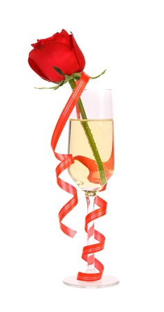 Red rose in glass of champagne and paper streamer. White background. photo