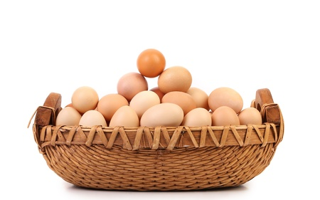 Brown eggs in the basket on a white photo