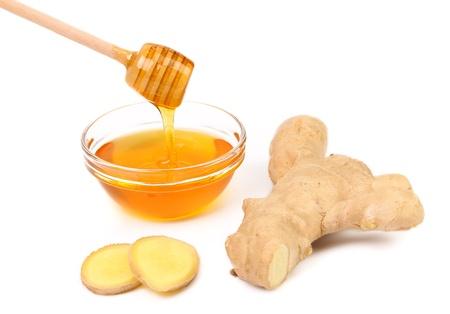 Miele in ciotola e una radice di zenzero fette. Sfondo bianco.