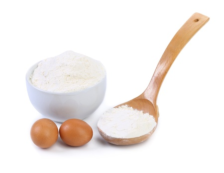 Spoon and bowl with flour, two brown eggs photo