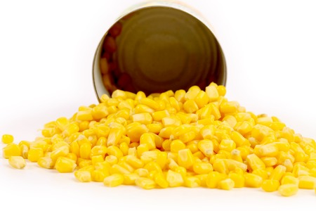 Opened cans and pilr of corn. Isolated on a white background. photo