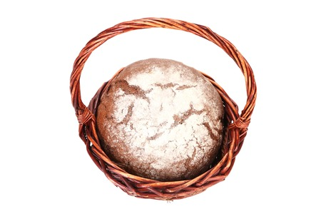 Brown bread in wicker basket. Isolated on a white background. photo