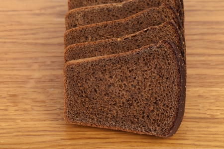 Slices of brown bread on a wooden table. Close up. photo
