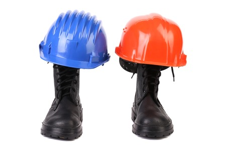 Hard hats and working boots. Isolated on a white background. photo